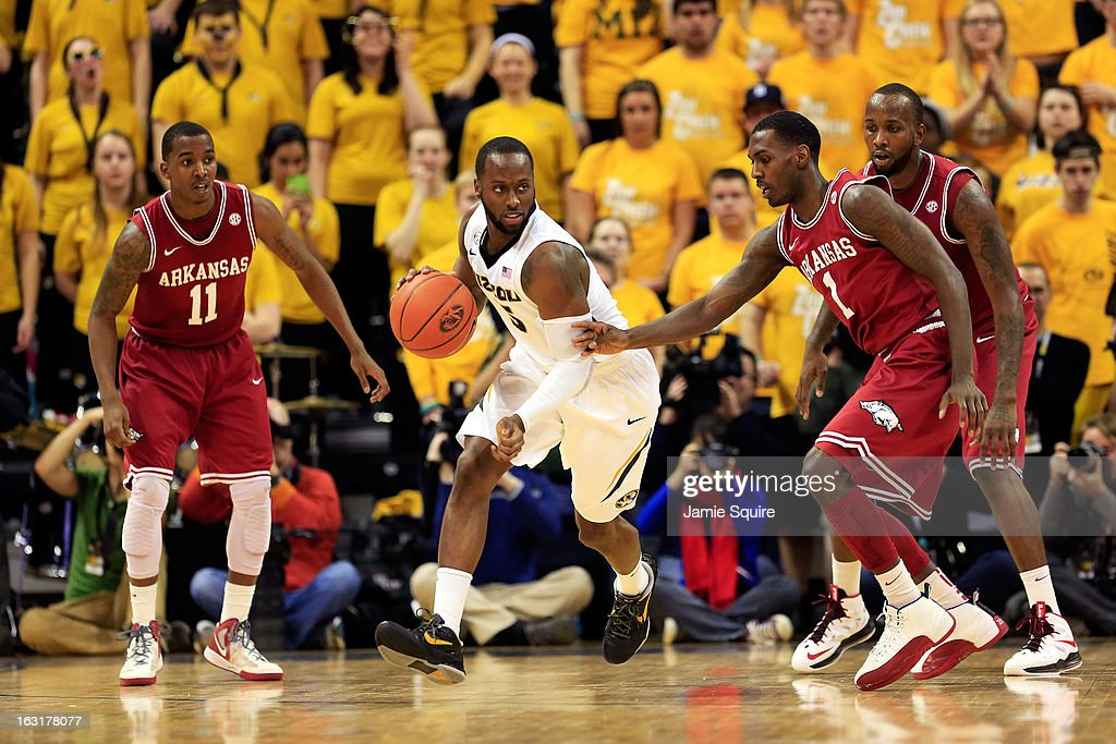 Keion Bell #5 of the Missouri Tigers controls the ball as BJ Young #11 and Mardracus Wade #1 of the Arkansas Razorbacks defend during the game at Mizzou Arena on March 5, 2013 in Columbia, Missouri.