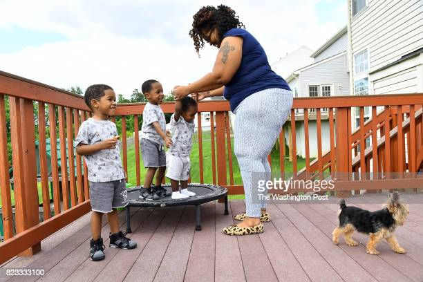 Keisha Carney helps Mekhi her Esure baby play with his siblings Malik left and Khalil while Diggy the dog checks out who is at the door May 26 2017...