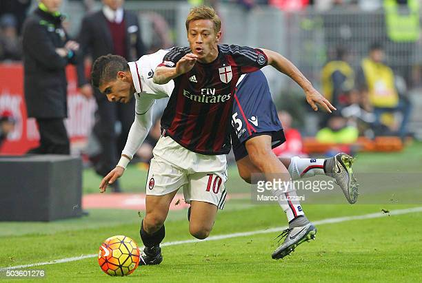 Keisuke Honda of AC Milan competes for the ball with Adam Masina of Bologna FC of Bologna FC during the Serie A match between AC Milan and Bologna FC...