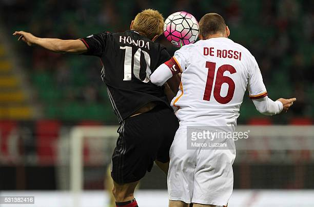Keisuke Honda of AC Milan competes for the ball with Daniele De Rossi of AS Roma during the Serie A match between AC Milan and AS Roma at Stadio...