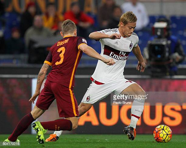 Keisuke Honda of AC Milan competes for the ball with Lucas Digne of AS Roma during the Serie A match between AS Roma and AC Milan at Stadio Olimpico...