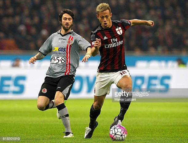 Keisuke Honda of AC Milan competes for the ball with Simone Branca of US Alessandria during the TIM Cup match between AC Milan and US Alessandria at...