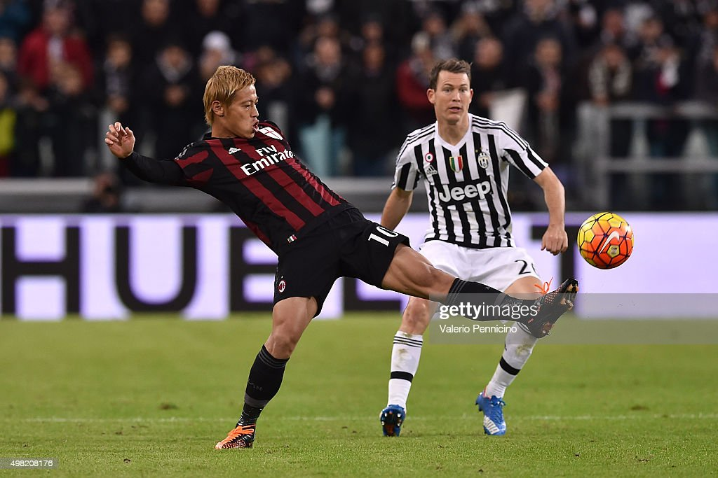 Keisuke Honda (L) of AC Milan in action against Stephan Lichtsteiner of Juventus FC during the Serie A match between Juventus FC and AC Milan at Juventus Arena on November 21, 2015 in Turin, Italy.