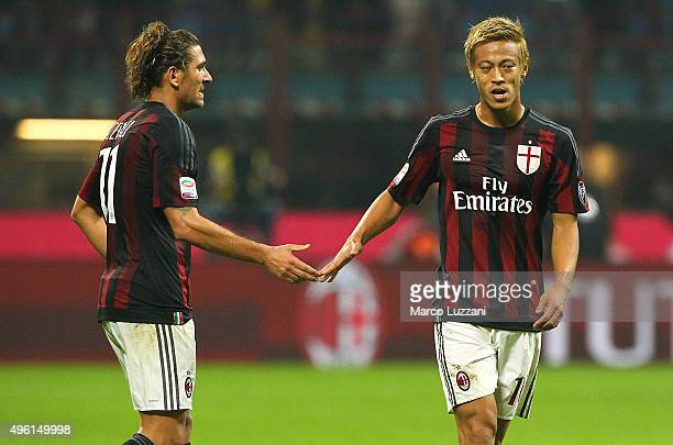 Keisuke Honda of AC Milan shakes hands with his teammate Alessio Cerci at the end of the Serie A match between AC Milan and Atalanta BC at Stadio...