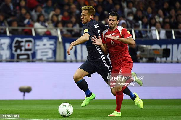 Keisuke Honda of Japan and Mhd Zahir Algunami Almedani of Syria compete for the ball during the FIFA World Cup Russia Asian Qualifier second round...