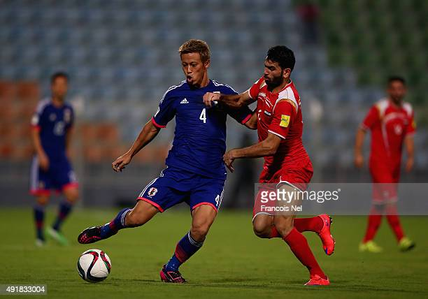 Keisuke Honda of Japan battles for the ball with Zahir Algunamiod Syria during the 2018 FIFA World Cup Asian Group E qualifying match between Syria...