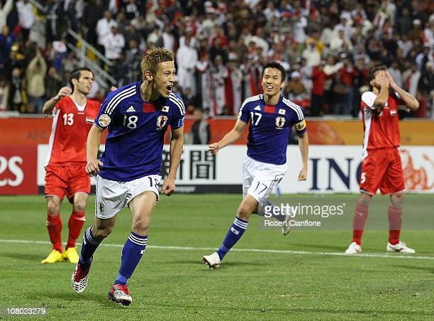 Keisuke Honda of Japan celebrates scoring his penalty during the AFC Asian Cup Group B match between Syria and Japan at Qatar Sports Club Stadium on...