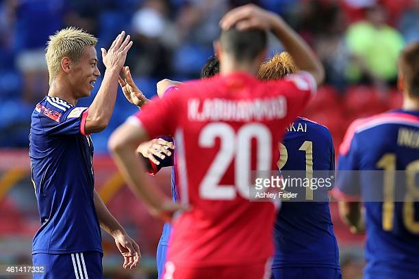 Keisuke Honda of Japan celebrates scoring his team's third goal with team mates during the 2015 Asian Cup match between Japan and Palestine at Hunter...