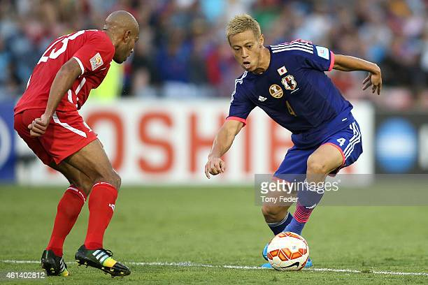 Keisuke Honda of Japan contests the ball with Masaaki Higashiguchi of Palestine during the 2015 Asian Cup match between Japan and Palestine at Hunter...