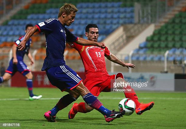 Keisuke Honda of Japan has his shot at goal blocked by Nadim Sabag of Syria during the 2018 FIFA World Cup Asian Group E qualifying match between...
