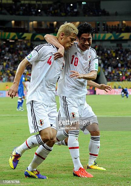 Keisuke Honda of Japan is congratulated by his teammate Shinji Kagawa after scoring the opening goal from a penalty during the FIFA Confederations...