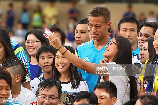 Keisuke Honda of Japan poses with children as the team pose for a group photo with children from the local community during a Japan training session...