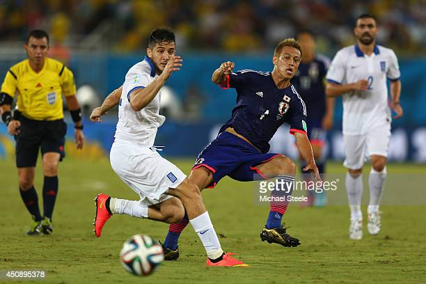 Keisuke Honda of Japan threads a pass during the 2014FIFA World Cup Group C match between Japan and Greece at Estadio das Dunas on June 19 2014 in...