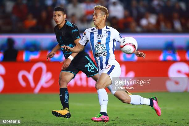 Keisuke Honda of Pachuca struggles for the ball with Alexis Perez of Queretaro during the 16th round match between Pachuca and Queretaro as part of...