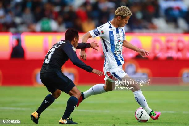 Keisuke Honda of Pachuca struggles for the ball with Jose Vazquez of Chivas during the 8th round match between Pachuca and Chivas as part of the...