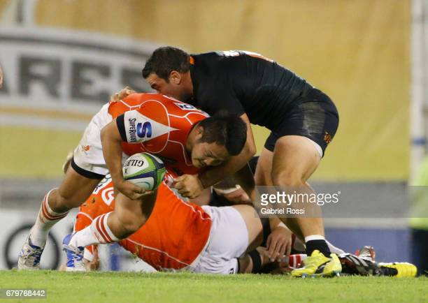 Keisuke Uchida of Sunwolves is tackled by Agustin Creevy of Jaguares during the Super Rugby match between Jaguares and Sunwolves at Estadio Jose...