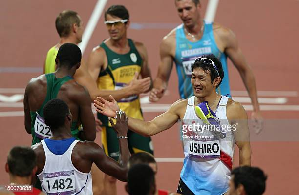 Keisuke Ushiro of Japan shakes hands with Leonel Suarez of Cuba as they celebrates while walking around the stadium after the Men's Decathlon on Day...