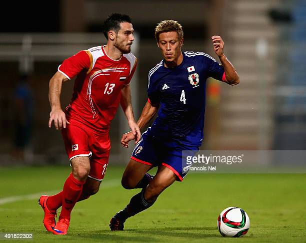 Keisuku Honda of Japan battles for the ball with Nadim Sabag of Syria during the 2018 FIFA World Cup Asian Group E qualifying match between Syria and...