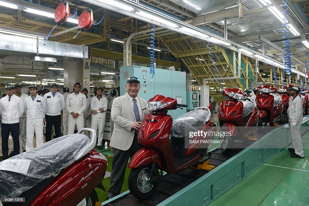 Keita Muramatsu, (C), president and CEO of Honda Motorcycle and Scooter India (HMSI), poses with employees at the second assembly line of Honda's fourth plant in India at Vithalapur, some 80 kms from Ahmedabad on June 29, 2016. The second assembly line was inaugurated June 29 by Keita Muramatsu, president and CEO of Honda Motorcycle and Scooter India (HMSI). Production expands by 0.6 million units to 1.2 million units annually at India's fourth plant at Vithalapur in Gujarat. / AFP / SAM