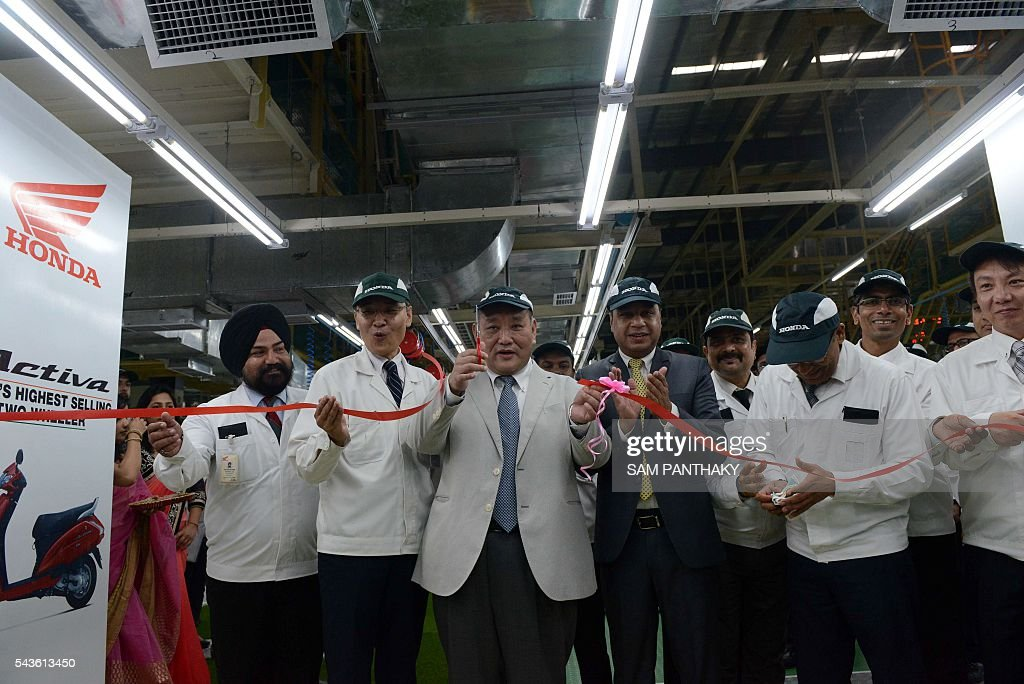 Keita Muramatsu, president and CEO of Honda Motorcycle and Scooter India (HMSI), (C), raises scissors as Masahiko Inaba, EVP - Vithalapur Plant, (HMSI), (2L) and Yadvinder Singh Guleria, Senior VP - Sales & Marketing, (HMSI) (C-R) look on during the ribbon cutting ceremony of the second assembly line of Honda's fourth plant in India at Vithalapur, some 80 kms from Ahmedabad on June 29, 2016. The second assembly line was inaugurated June 29 by Keita Muramatsu, president and CEO of Honda Motorcycle and Scooter India (HMSI). Production expands by 0.6 million units to 1.2 million units annually at India's fourth plant at Vithalapur in Gujarat. / AFP / SAM