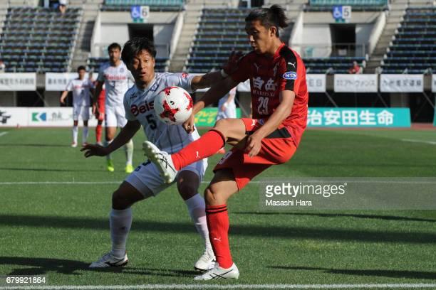Keita Saito of Roasso Kumamoto and Takumi Abe of Thespa Kusatsu Gunma compete for the ball during the JLeague J2 match between Roasso Kumamoto and...