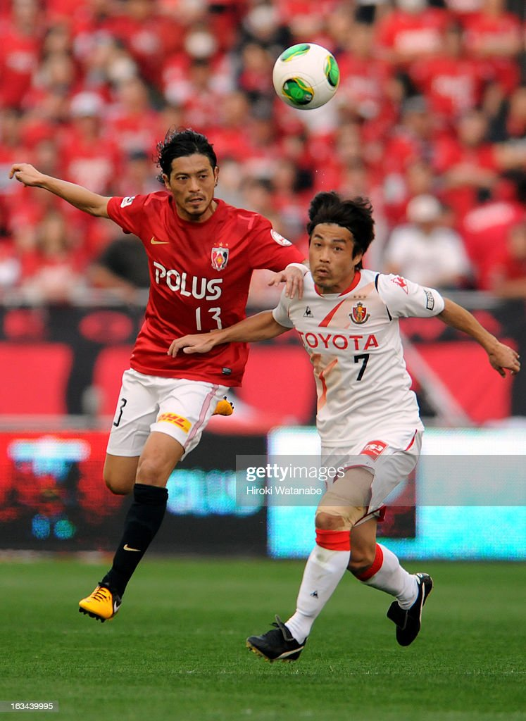 Keita Suzuki of Urawa Red Diamonds and <a gi-track='captionPersonalityLinkClicked' href=/galleries/search?phrase=Naoshi+Nakamura&family=editorial&specificpeople=5818461 ng-click='$event.stopPropagation()'>Naoshi Nakamura</a> of Nagoya Grampus compete for the ball during the J.League match between Urawa Red Diamonds and Nagoya Grampus at Saitama Stadium on March 9, 2013 in Saitama, Japan.