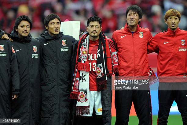 Keita Suzuki of Urawa Red Diamonds poses for photographs with his team mates during his retimerement ceremony after the JLeague match between Urawa...