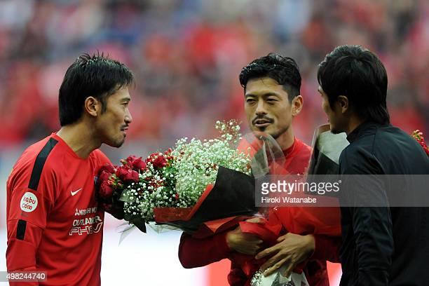 Keita Suzuki of Urawa Red Diamonds receives flower bunch from his team mates Yuki Abe and Daisuke Nasu during his retimerement ceremony after the...