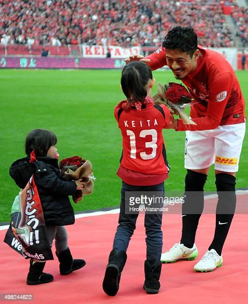 Keita Suzuki of Urawa Red Diamonds receives flower bunches from his children during his retirement ceremony after the JLeague match between Urawa Red...