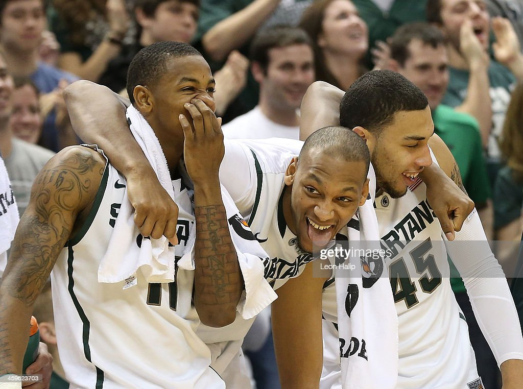 Keith Appling #11 <a gi-track='captionPersonalityLinkClicked' href=/galleries/search?phrase=Adreian+Payne&family=editorial&specificpeople=7367769 ng-click='$event.stopPropagation()'>Adreian Payne</a> #5 and Denzel Valentine #45 of the Michigan State Spartans celebrate a win over the New Orleans Privateers at the Breslin Center on December 28, 2013 in East Lansing, Michigan. The Spartans defeatede the Privateers 101-48.