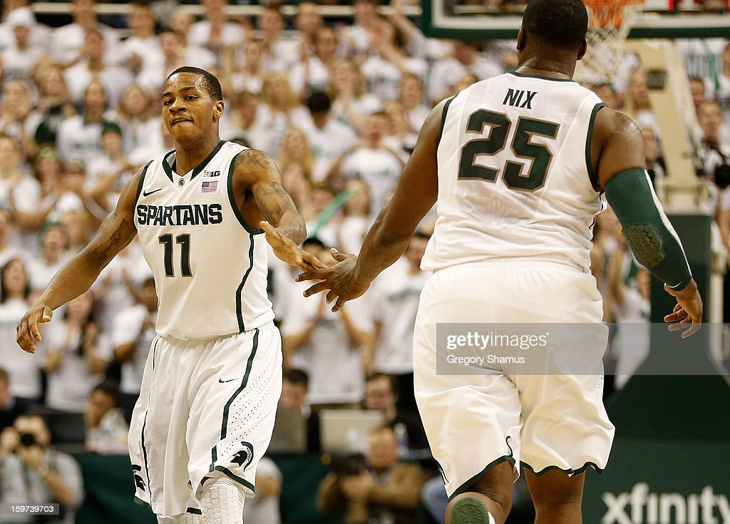 Keith Appling #11 of the Michigan State Spartans celebrates a first-half basket with Derrick Nix #25 during action against the Ohio State Buckeyes at the Jack Breslin Center on January 19, 2013 in East Lansing, Michigan. Michigan State won the game 59-56.