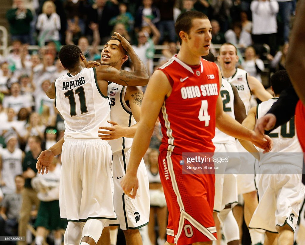 Keith Appling #11 of the Michigan State Spartans celebrates with Denzel Valentine #45 during action against the Ohio State Buckeyes at the Jack Breslin Center on January 19, 2013 in East Lansing, Michigan. Michigan State won the game 59-56.