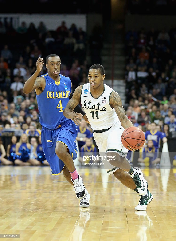 Keith Appling of the Michigan State Spartans dribbles past Jarvis Threatt of the Delaware Fightin Blue Hens during the second round of the 2014 NCAA...