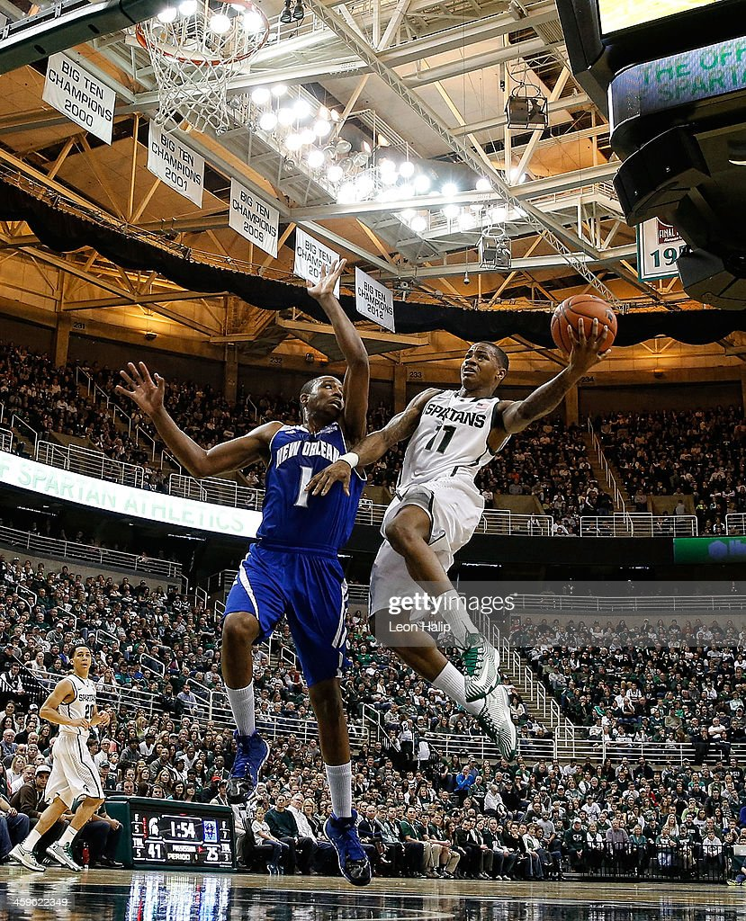 Keith Appling #11 of the Michigan State Spartans drives the ball to the basket during the first half of the game as Tevin Broyles #1 of the New Orleans Privateers defends at the Breslin Center on December 28, 2013 in East Lansing, Michigan.