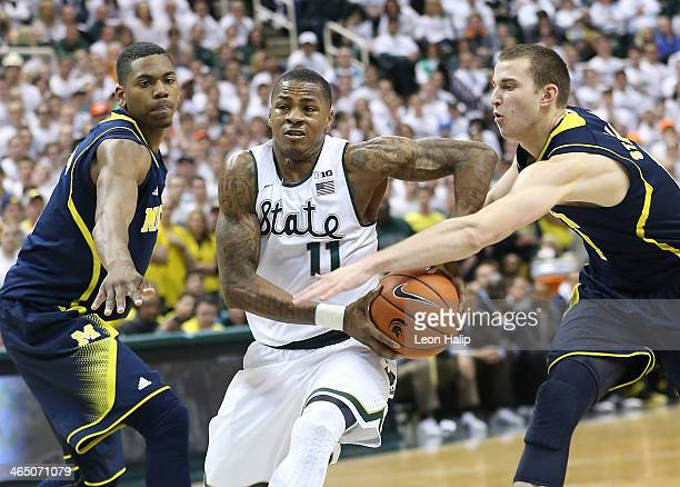 Keith Appling of the Michigan State Spartans drives the ball to the basket as Glenn Robinson III and Nik Stauskas of the University of Michigan...
