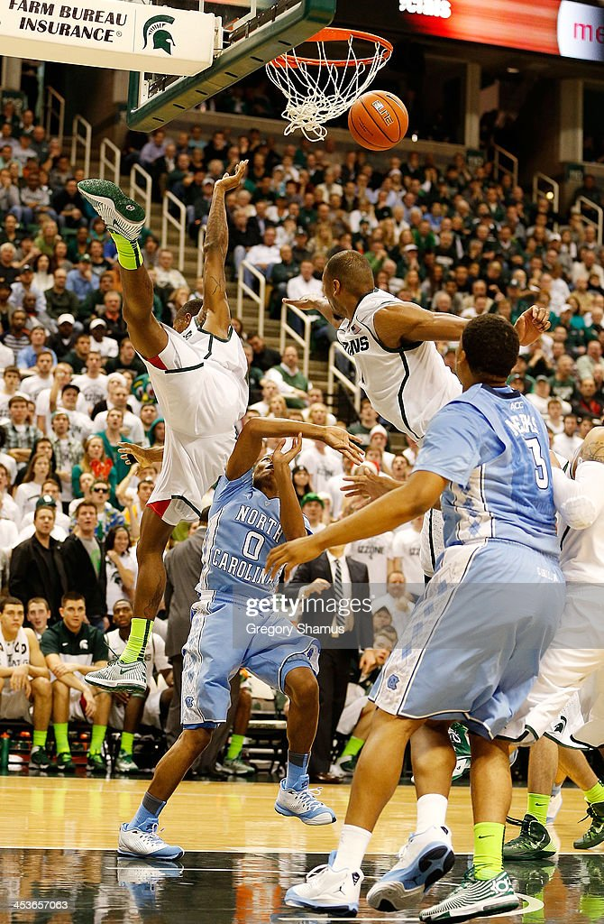 Keith Appling #11 of the Michigan State Spartans flies through the air trying to bock the shot of Nate Britt #0 of the North Carolina Tar Heels during the first half at the Jack T. Breslin Student Events Center on December 4, 2013 in East Lansing, Michigan. North Carolina won the game 79-65.