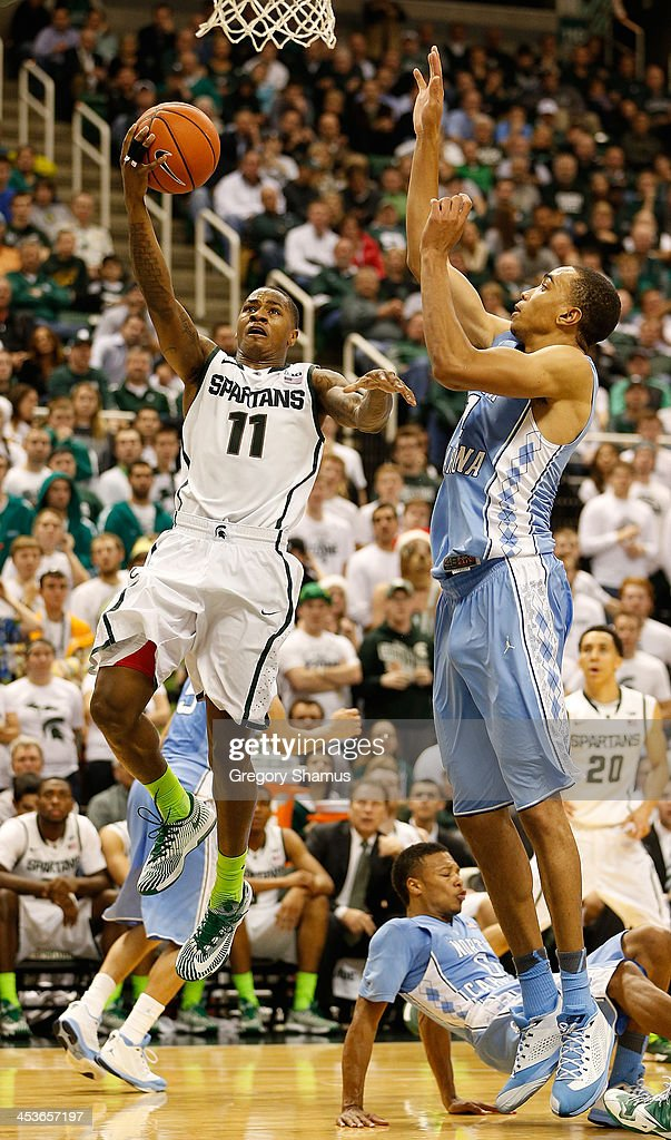 Keith Appling #11 of the Michigan State Spartans gets to the basket past Brice Johnson #11 of the North Carolina Tar Heels during the second half at the Jack T. Breslin Student Events Center on December 4, 2013 in East Lansing, Michigan. North Carolina won the game 79-65.