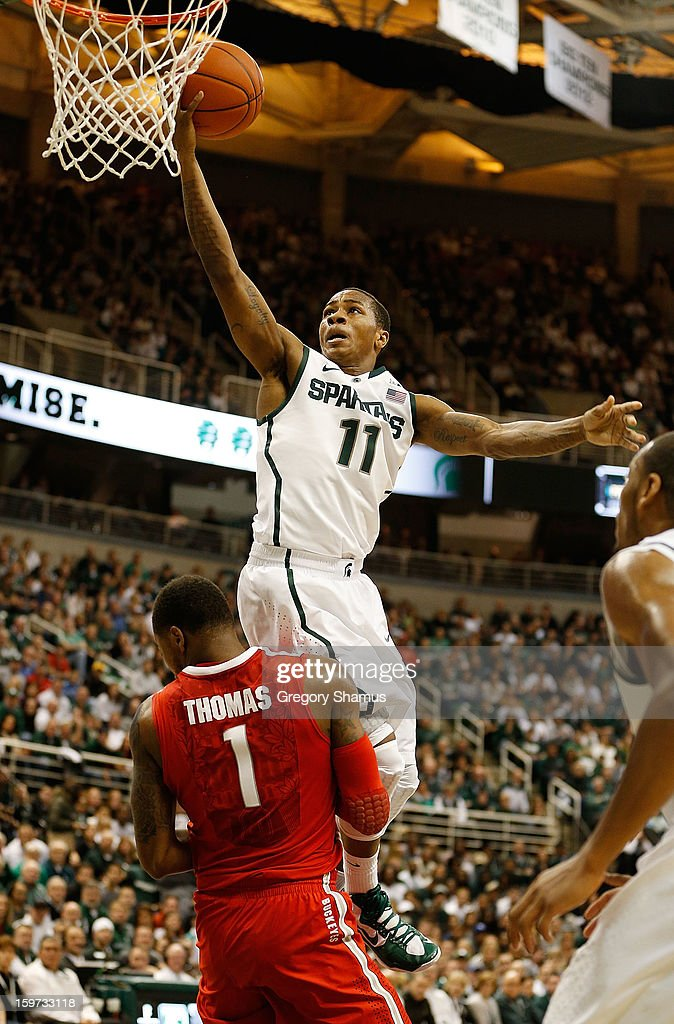 Keith Appling #11 of the Michigan State Spartans goes up for a shot over Deshaun Thomas #1 of the Ohio State Buckeyes, but was called for a charge in the first half at the Jack Breslin Center on January 19, 2013 in East Lansing, Michigan.