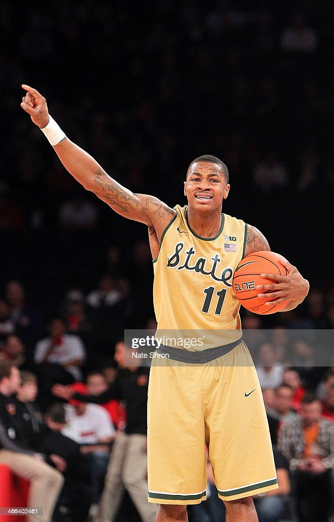 Keith Appling #11 of the Michigan State Spartans points as he holds the ball and signals to teamates during the game against the Georgetown Hoyas at Madison Square Garden on February 1, 2014 in New York City.
