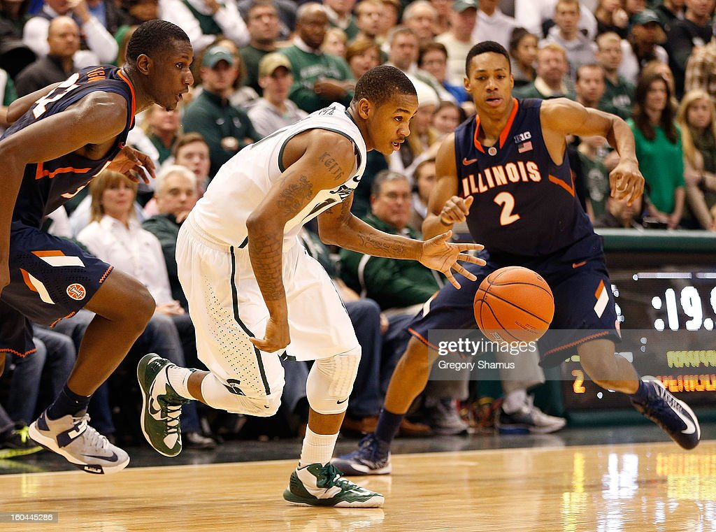 Keith Appling #11 of the Michigan State Spartans splits the defense of Joseph Bertrand #2 and Nnanna Egwu #32 of the Illinois Fighting Illini during the second half at the Jack T. Breslin Student Events Center on January 31, 2013 in East Lansing, Michigan. Michigan State won the game 80-75.