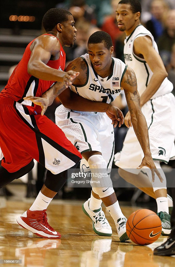 Keith Appling #11 of the Michigan State Spartans tries to dribble around Bryant Mbamalu #0 of the Louisiana-Lafayette Ragin' Cajuns during the second half at the Jack T. Breslin Student Events Center on November 25, 2012 in East Lansing, Michigan. Michigan State won the game 63-60.