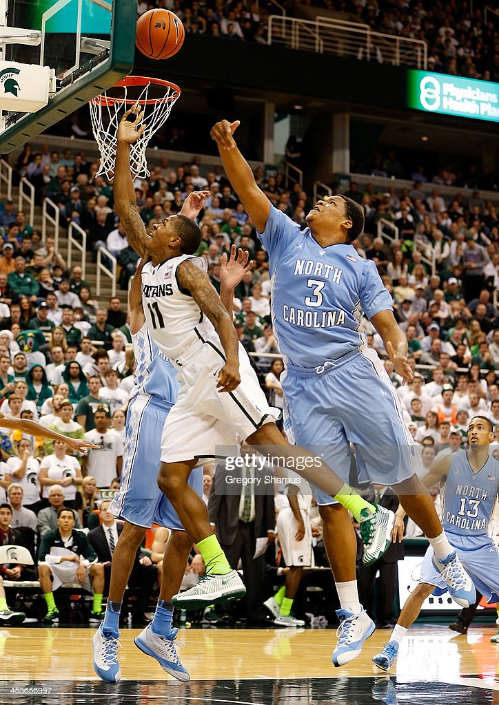 Keith Appling #11 of the Michigan State Spartans tries to get a second half shot off around Kennedy Meeks #3 of the North Carolina Tar Heels at the Jack T. Breslin Student Events Center on December 4, 2013 in East Lansing, Michigan. North Carolina won the game 79-65.