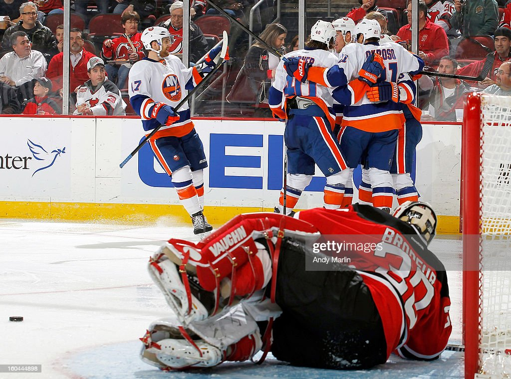 Keith Aucoin #10 of the New York Islanders is congratulated by his teammates after scoring a second-period goal as Martin Brodeur #30 of the New Jersey Devils lays on the ice during the game at the Prudential Center on January 31, 2013 in Newark, New Jersey.