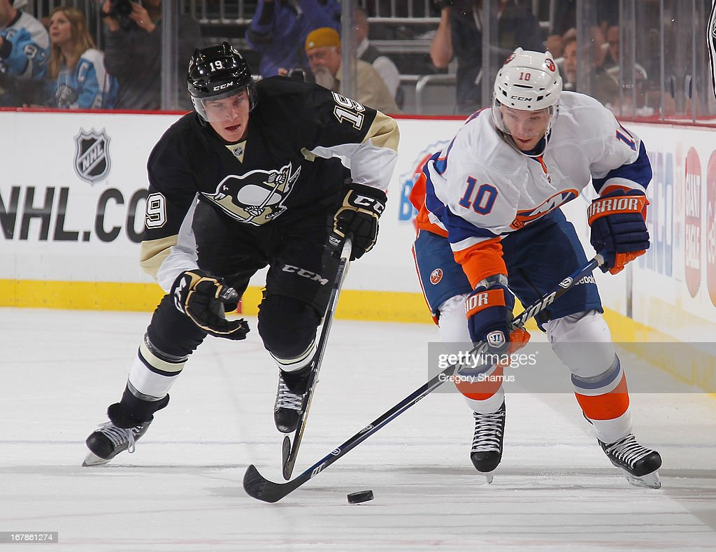 Keith Aucoin of the New York Islanders moves the puck in front of Beau Bennett of the Pittsburgh Penguins in Game One of the Eastern Conference...