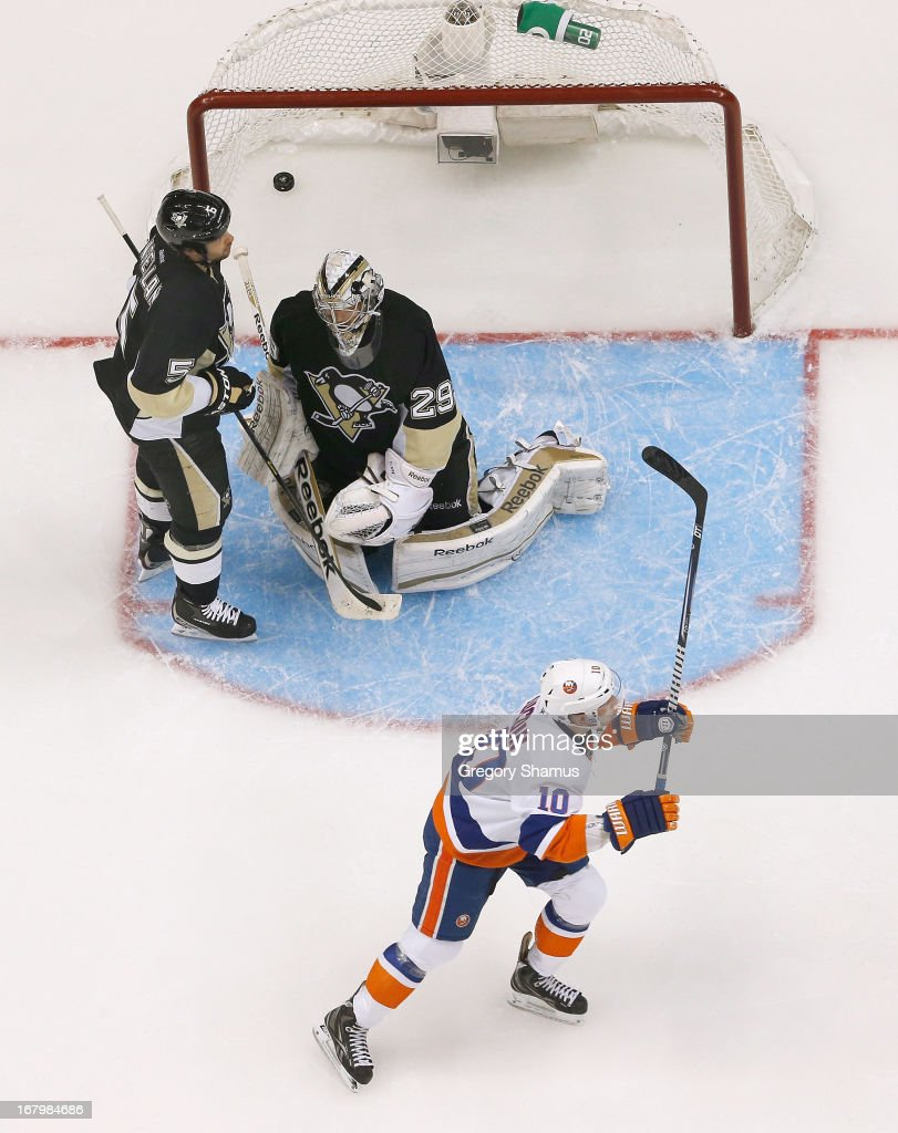 Keith Aucoin of the New York Islanders reacts after a goal by Colin McDonald against of Deryk Engelland and MarcAndre Fleury of the Pittsburgh...
