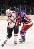 Keith Aucoin of the Washington Capitals controls the puck against Marian Gaborik of the New York Rangers in Game One of the Eastern Conference...