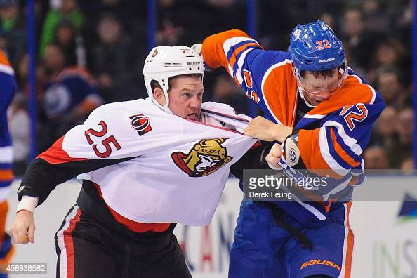 Keith Aulie of the Edmonton Oilers fights Chris Neil of the Ottawa Senators during an NHL game at Rexall Place on November 13 2014 in Edmonton...