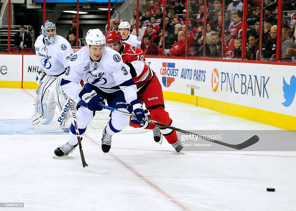 Keith Aulie #3 of the Tampa Bay Lightning and <a gi-track='captionPersonalityLinkClicked' href=/galleries/search?phrase=Jiri+Tlusty&family=editorial&specificpeople=543236 ng-click='$event.stopPropagation()'>Jiri Tlusty</a> #19 of the Carolina Hurricanes chase for the puck during play at PNC Arena on January 22, 2013 in Raleigh, North Carolina.