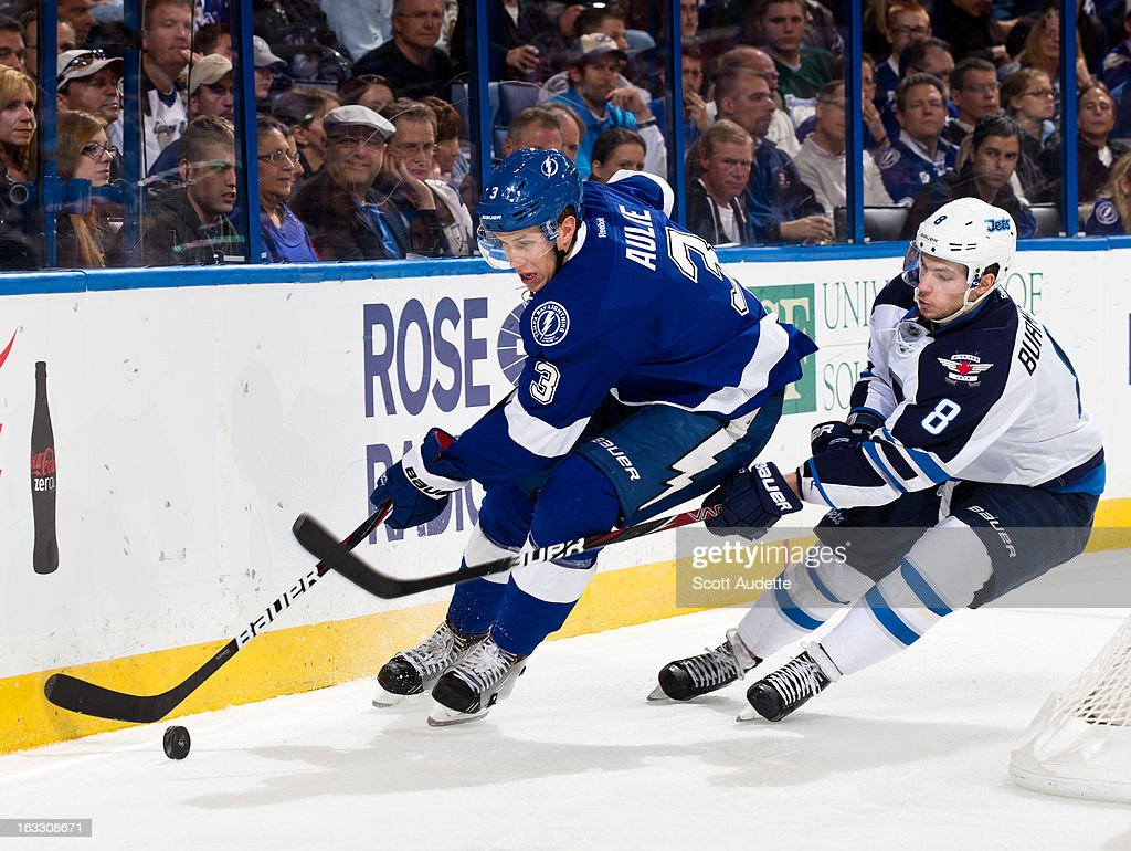 Keith Aulie #3 of the Tampa Bay Lightning moves the puck while guarded by Alex Burmistrov #8 of the Winnipeg Jets during the second period of the game at the Tampa Bay Times Forum on March 7, 2013 in Tampa, Florida.