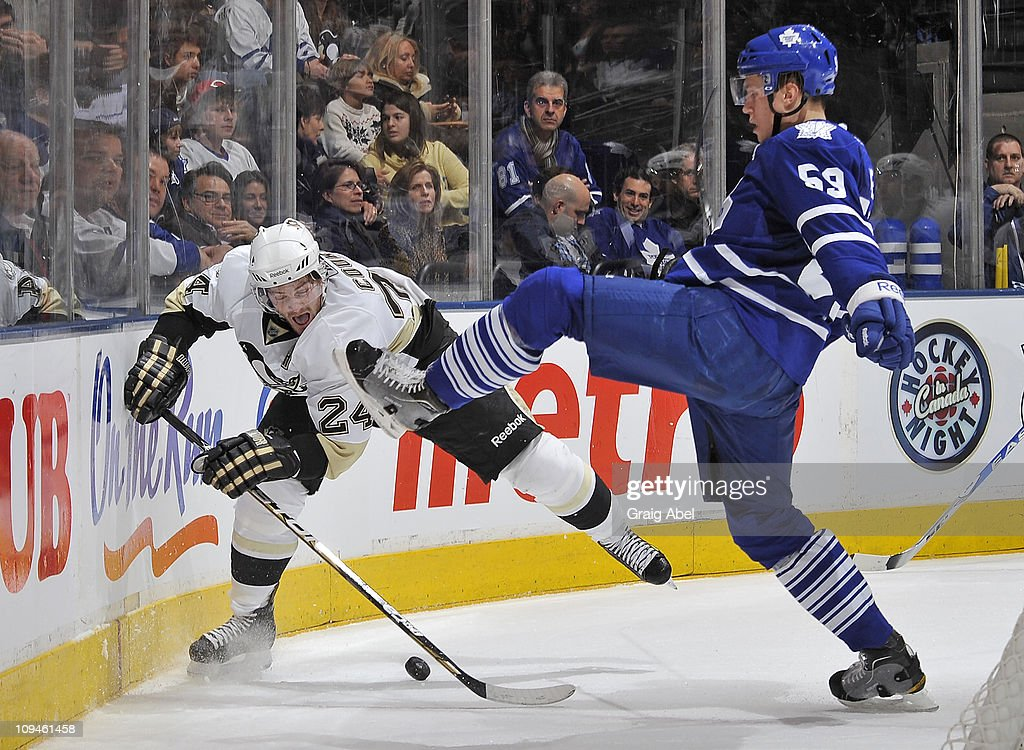 Keith Aulie of the Toronto Maple Leafs battles for the puck with Matt Cooke of the Pittsburgh Penguins February 26 2011 at the Air Canada Centre in...